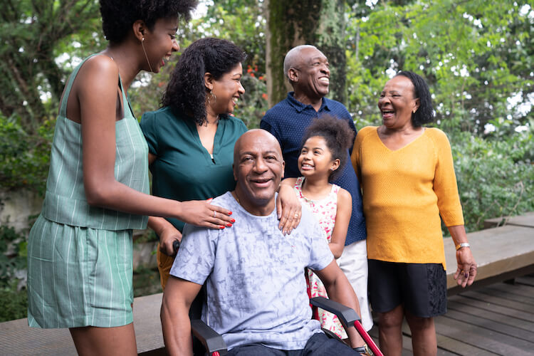 man in wheelchair surrounded by his family and friends