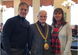 two men and a woman post for a photo. the man in the middle is a dignitary from Scotland and is wearing a gold medallion