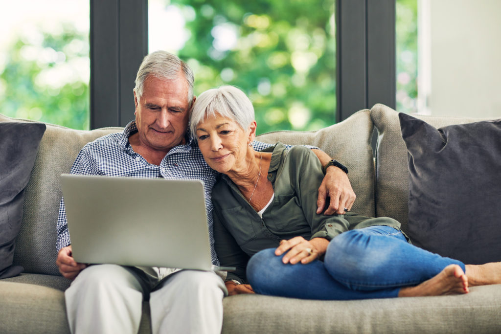 Shot of a senior couple using a laptop on the sofa at home