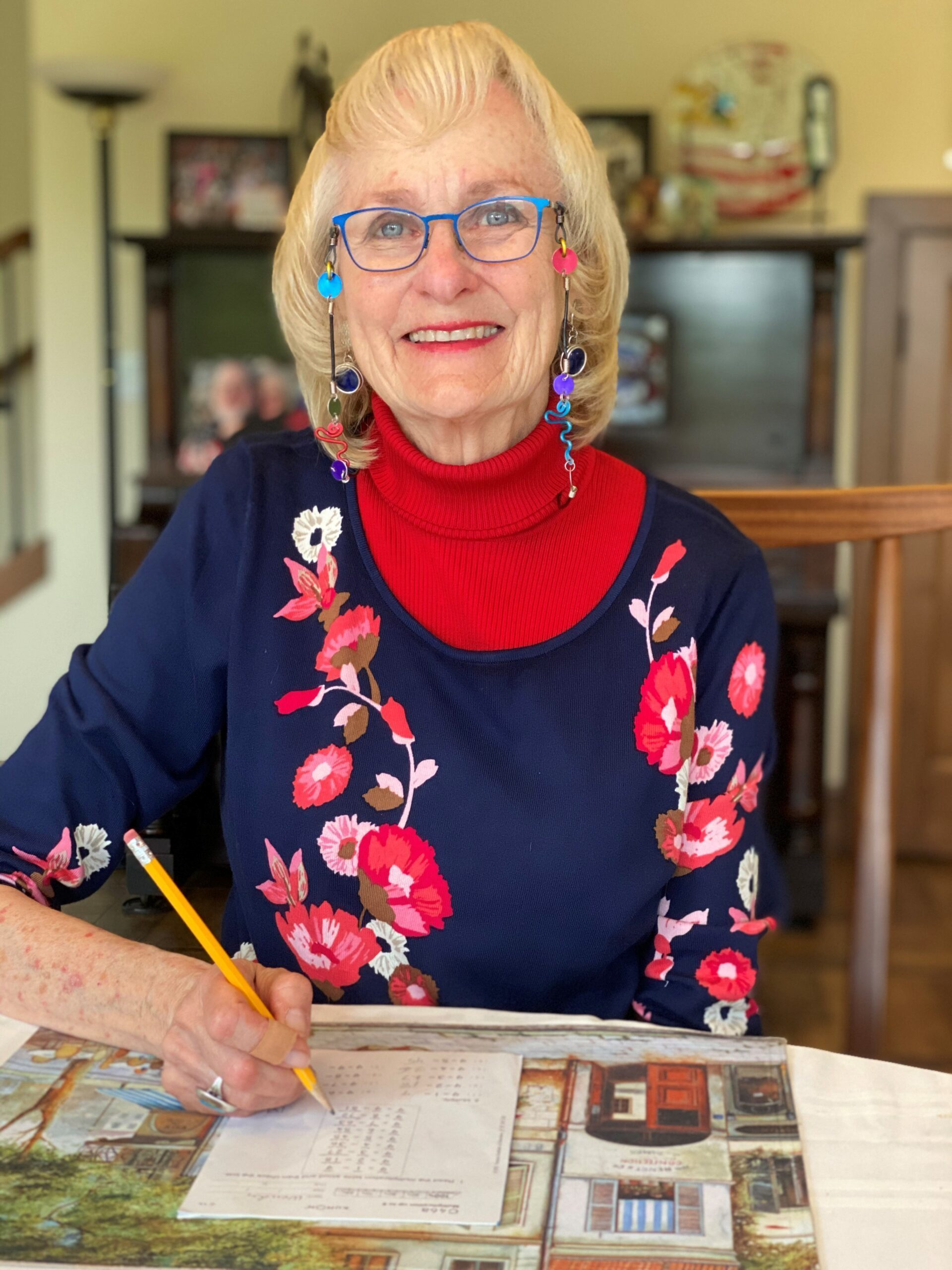 photo of an older woman in glasses. She is smiling as she works on a writing task
