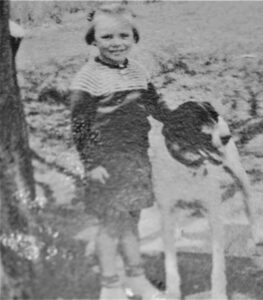 old, black and white photo of a young girl and her dog