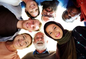 a group of people from all races and ages are in a circle smiling and looking at the camera