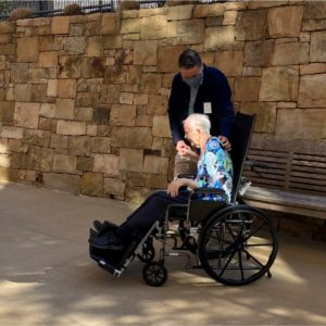 a woman in a wheel chair gets a back scratch from her son during a visit outdoors