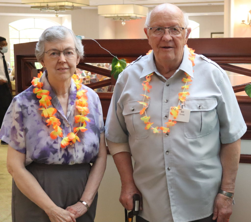 a wife and husband pose for a photo at a Hawaiian event