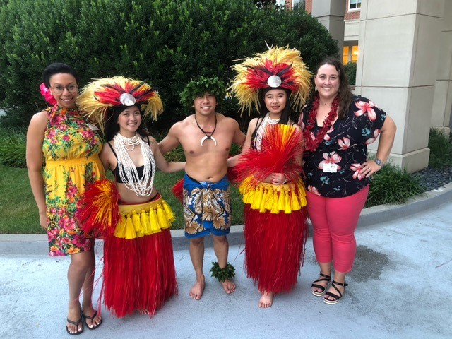 A group of happy people at a Hawaiian event share a moment